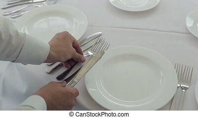 The waiter puts on a table for the banquet cutlery - The...
