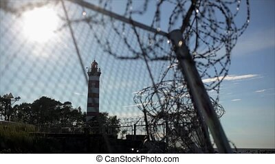 Barbed wire fence under sun focus in out.  Summer. Jail. Lighthouse background