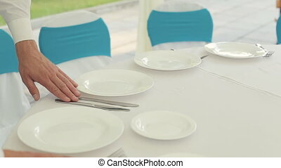 The waiter gently corrects cutlery on the table with a white...