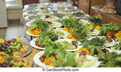 Many different dishes with vegetables, fruits on a large platters on a banquet