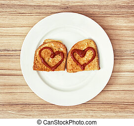 Two fried breads in the egg with hearts of ketchup,...