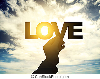 Love - Paper words in wooman hands on sky background