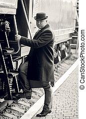 Monochrome photo of man in bowler hat walking inside of...