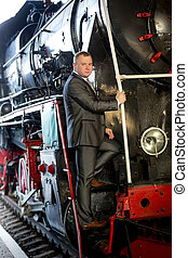 man posing on the stairs of old steam train - Elegant man...