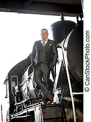 man in gray suit posing on retro train - Young man in gray...