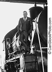 Black and white photo of man in retro suit standing on old...