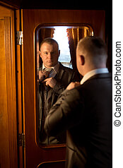 Toned portrait of gentleman looking in mirror and getting...