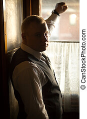 Toned portrait of businessman leaning on window in train