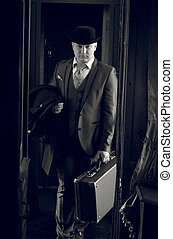 Monochrome photo of man in hat with suitcase walking in the...