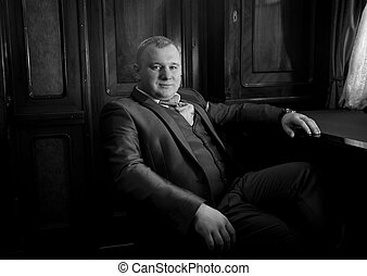 portrait of stylish man in retro suit sitting in armchair at...
