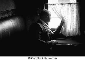 Monochrome portrait of man sitting in train coupe and...