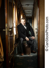Toned shot of man in vintage suit posing in train - Toned...