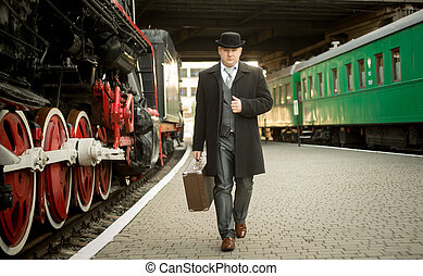 man in retro suit with suitcase walking on the train...