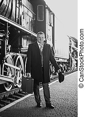 Black and white retro photo of man in suit waiting for train...