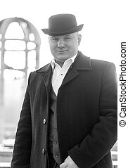 Black and white portrait of smiling gentleman in bowler hat...
