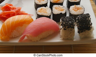 Various sushi on white plate on wooden background - various...