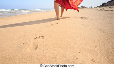 Closeup Girl in Long Red Dress Leaves Footprints on Wet Sand...
