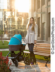 Young mother posing with baby stroller at sunny day -...
