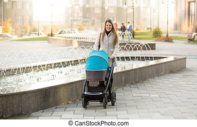 Happy mother with baby stroller walking on street near...