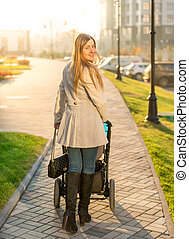 Beautiful woman walking with baby stroller at park
