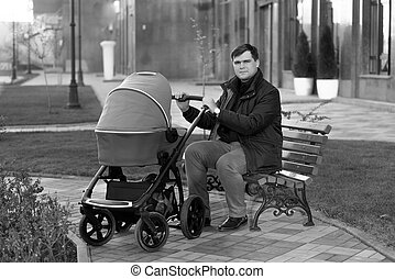father sitting on bench at park with baby stroller - Young...