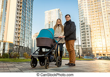Happy family walking with pram on street at sunny day -...