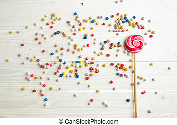 Lots of colorful little candies and lollipop on white wooden background