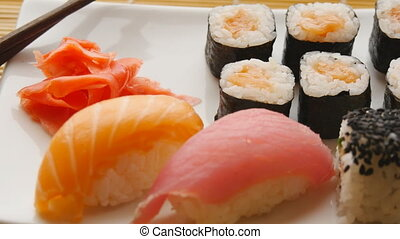 Various sushi on white plate on wooden background