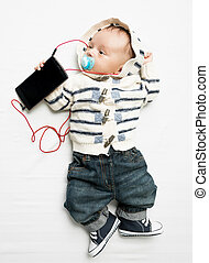 Funny photo of baby boy listening to music on phone with earphones