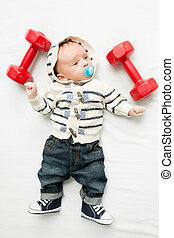 baby boy lying on bed with dumbbells