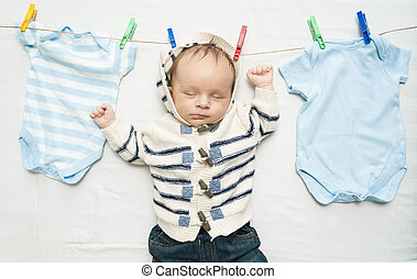 cute baby boy hanging on clothesline next to drying clothes...
