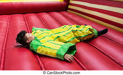 The boy in colorful plastic dress is lying in the bouncy castle