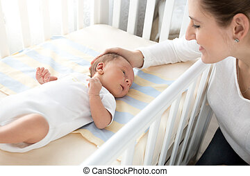 happy smiling mother caressing her baby lying in cot