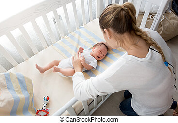 Mother sitting near the cradle and holding baby's hand -...
