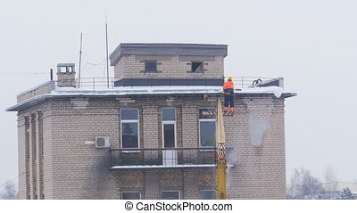 Cleaning snow from the roof in winter