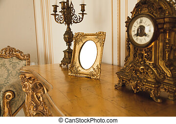 Antique golden frame on table at luxurious interior -...
