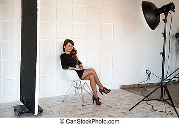 Beautiful woman posing on chair at professional photostudio...