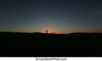 Romantic Couple with Tandem Bicycles Kissing While Sunset....
