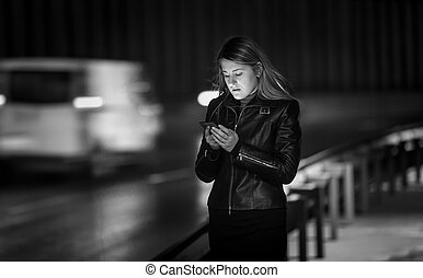 Black and white portrait of woman typing message on street...