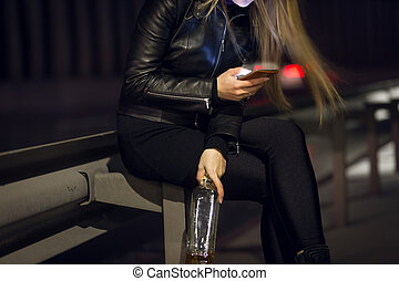 Closeup of woman sitting at night on street and typing...