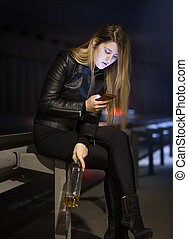 caucasian woman drinking alcohol and typing message on...