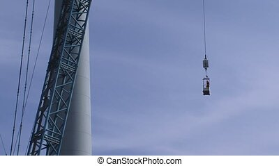 Wind turbine personnel hoist cage moves upward along turbine...
