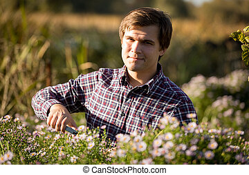 portrait of young smiling man pruning flowers at garden