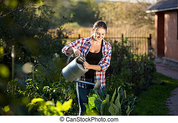 brunette woman watering plants at kitchen garden - Young...