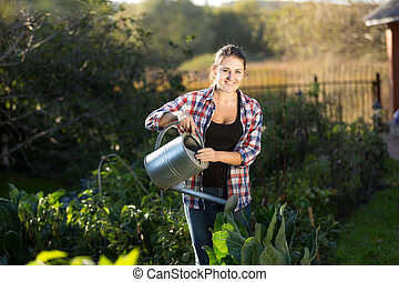 young woman watering plants at garden at sunny day - Smiling...