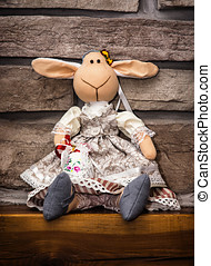 Handmade Easter textil sheep with painted egg on the wooden...