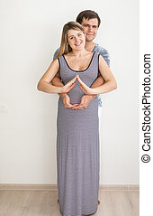 Toned photo of couple holding hands in shape of house