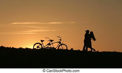 Romantic Couple with Tandem Bicycles Kissing While Sunset -...