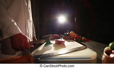 Chef in restaurant beat off meat on table. Vegetables. Spotlight. Agression
