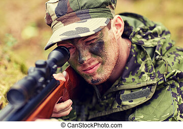soldier or hunter shooting with gun in forest - hunting,...